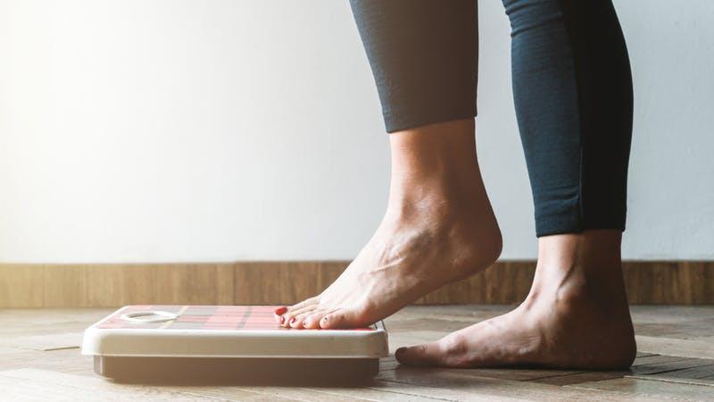 Femme vérifiant ses kilogrammes en montant sur la balance - concept de soin de soi et de positivité corporelle - flambée chaude à gauche